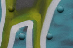 Metal wall with rivets and graffiti. Close up view of a metal surface with rivets and colorful graffiti royalty free stock images