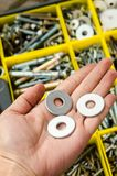 Metal washer in hand on the background of tools royalty free stock photography