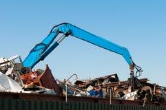 Metal waste. Blue crane picking up waste Stock Photo