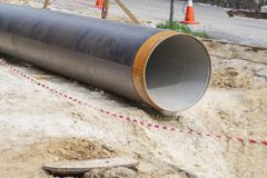 Metal water pipe, large diameter, prepared for laying for sewer. Lying on the street stock images