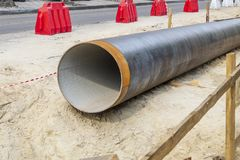 Metal water pipe, large diameter, prepared for laying for sewer. Lying on the street stock photo
