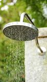 Metal water shower in open outdoors at a hotel spa Stock Photos