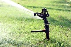 A metal water sprinkler. Is watering the garden Stock Image