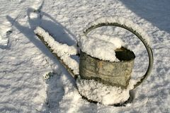 Metal watering can covered in snow in winter afternoon sun Stock Photography