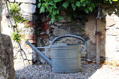 Metal watering can on gravel in front of the wall Stock Images