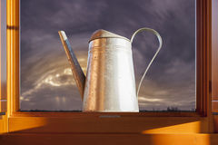 Metal watering can over open window Royalty Free Stock Image