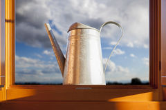 Metal watering can over open window Royalty Free Stock Photo