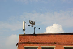 Metal weather vane on the roof of the building. Weather vane in the form of a double-headed eagle symbol of the Russian Empire on the roof royalty free stock images