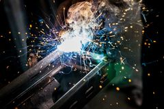 Metal welding with sparks and smoke on dark background.  Stock Photo