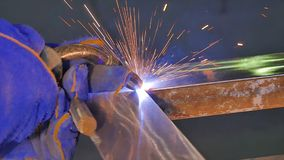 Metal Welding with sparks and smoke. Worker with protective mask welding metal. Welder joins metal parts. A process. Using a semi-automatic welding. Welding Stock Image