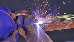 Metal Welding with sparks and smoke. Worker with protective mask welding metal. Welder joins metal parts. A process. Using a semi-automatic welding. Welding Stock Photography