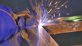 Metal Welding with sparks and smoke. Worker with protective mask welding metal. Welder joins metal parts. A process. Using a semi-automatic welding. Welding Royalty Free Stock Image