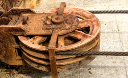 Metal wheel of a old shipyard ramp disused. Detail of a rusty drag metal wheel with its cable of a old shipyard ramp disused Royalty Free Stock Images