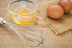 Metal whisk and fresh egg Stock Photo
