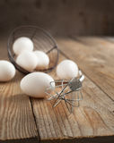 Metal whisk and fresh eggs Stock Photography
