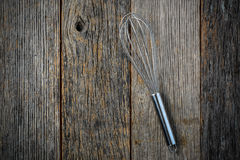 Metal Whisk on Rustic Wood Background Stock Image