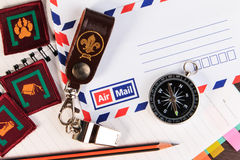 Metal whistle with leather key chain, compass, badge on envelopes. Background. A close up view royalty free stock photo