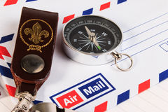 Metal whistle with leather key chain, compass, badge on envelopes. Background. A close up view stock photo