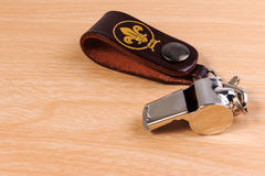 Metal whistle with leather key chain on wooden background. Stock Photos