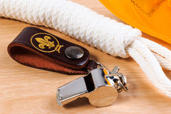 Metal whistle, yellow scout scarf and scout rope on wooden background. Stock Photos