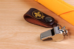 Metal whistle with yellow scout scarf on wooden background. Stock Photo