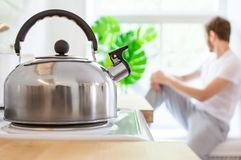Metal kettle on electric stove. In the background, a young man sits on the windowsill. Good morning concept stock photography