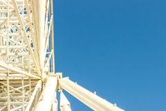 Metal white frame of a ferris wheel on a blue sky background. Ab. Stractive fragment of architecture royalty free stock image