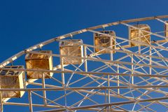 Metal white frame of a ferris wheel on a blue sky background. Ab. Stractive fragment of architecture royalty free stock photography