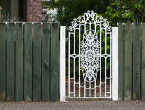 Metal White Gate. In a green wooden fence Royalty Free Stock Image