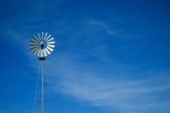 Metal windmill against blue sky. Aluminum colored windmill against blue sky with light clouds royalty free stock image