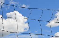 Metal wire fence against the bright blue sky - prevents crossing Royalty Free Stock Photo