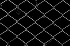 Metal wire fence or cage. With black background Stock Photos