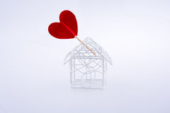 Metal wired house model and red heart shape Stock Photos
