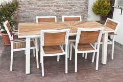 Metal and wood outdoor patio furniture for dining. Table and white chairs royalty free stock photo