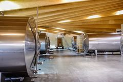 Wineries of La Rioja in Spain. Metal and wooden barrels to ferment wine in a cellar with lots of lighting and wooden ceiling in La Rioja in Spain stock photography