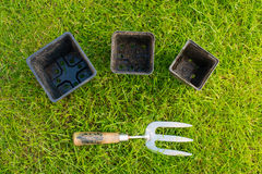Metal and Wooden Hand Fork and some Plant Pots. Worn metal and wooden garden hand fork and three black plastic plant pots on some green grass Stock Images