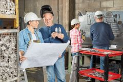 Metal worker with experience and apprentice. Planning metal construction royalty free stock photos