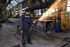 Metal worker grinds weld steel sections using an angle grinder. Stock Photos