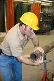 Metal Worker Measures Pipe. Metal worker using a flexible ruler to measure pipe and mark it for cutting.  Authentic and accurate content depiction in accordance Royalty Free Stock Image