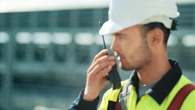 Metal worker in uniform and hard hat with walkie talkie medium close-up. Industrial foreman controls work at gas or oil production plant using walkie-talkie stock footage