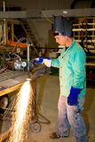 Metal Worker Using Track Burner. Metal worker in a factory using a track burner to cut a piece of metal.  Authentic and accurate content depiction with all work Stock Photo