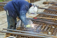 Metal worker welds a metal construction for cables royalty free stock photos