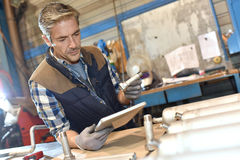 Metal worker working with help of tablet Stock Photos