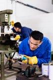 Metal workers in industrial workshop grinding Stock Images