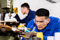 Metal workers in industrial workshop grinding Royalty Free Stock Images