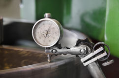 Metal workshop machine, dial gauge instrument measures inclination of cogwheel gear Stock Photography