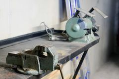 Metal workshop. Vise and bench grinder on metallic workbench stock photography