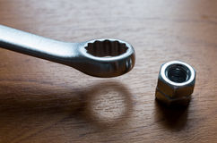 Metal wrench and nut. On a wooden background Stock Images