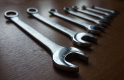 Metal wrenches. The Set of silver metal wrenches on a wooden background Royalty Free Stock Photos