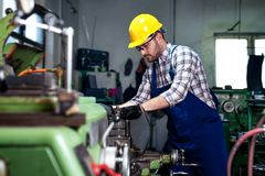 Metal worker turner operating lathe machine at industrial manufacturing factory. Metal young worker turner operating lathe machine at industrial manufacturing royalty free stock photos